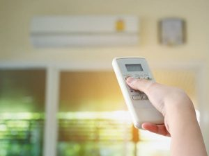Woman with Air Conditioner Remote Control